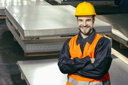 engineering clipboard: Smiling worker in protective uniform in front of sheet tin metal