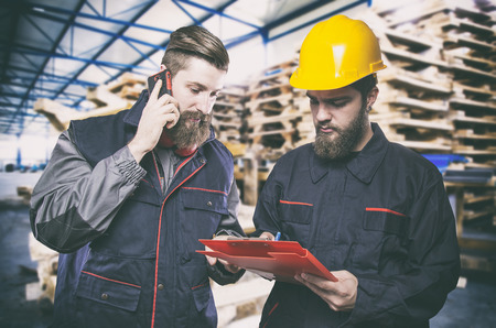 ear muff: Workers in protective uniform in front of wooden pallets