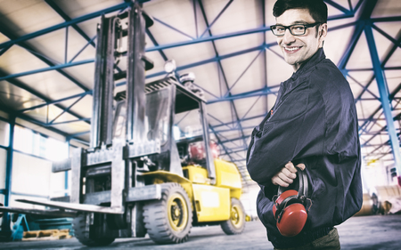 ear muff: Smiling worker in protective uniform in production hall in front of forklift  Stock Photo