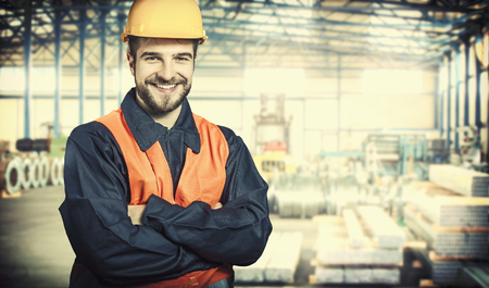 smiling worker in protective uniform and protective helmet in production hall  Stockfoto