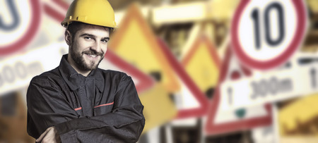 engineering clipboard: Worker in protective uniform and protective helmet in front of road signs