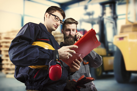 engineering clipboard: Workers in protective uniform in front of forklift