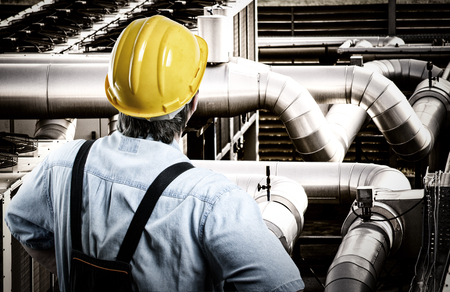 trabajador petroleros: Trabajador en uniforme de protección y casco de protección frente a las tuberías industriales