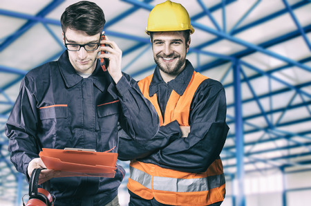 Smiling workers in protective uniforms in production hall  Stock Photo