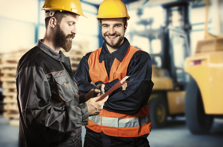 ear muff: Smiling workers in protective uniform in front of forklift  Stock Photo
