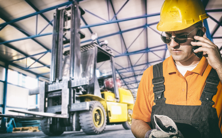 engineering clipboard: Worker in protective uniform in production hall in front of forklift