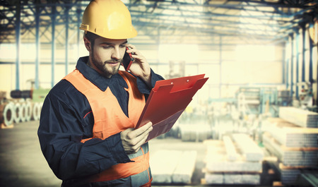engineering clipboard: Worker in protective uniform and protective helmet in production hall  Stock Photo