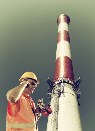 engineering clipboard: worker in protective uniform with smart phone, clipboard, protective helmet, protective gloves, and ear muffs in their hands in front of factory chimney
