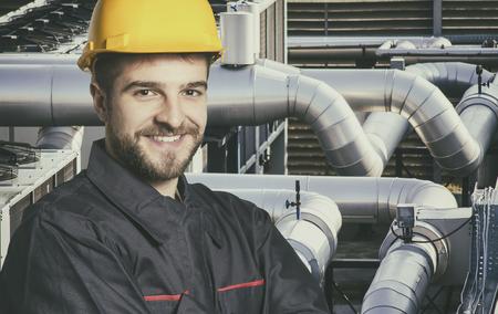 industria quimica: Trabajador sonriente en uniforme protector y casco de protección frente a las tuberías industriales - imagen de tonos, retro película se filtró en estilo Instagram