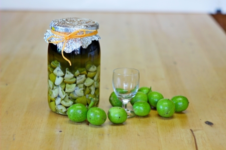 fresh green,young walnuts and bottle of homemade liqueur taken as remedy for stomach aches