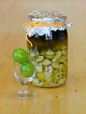 fresh green,young walnuts and bottle of homemade liqueur taken as remedy for stomach aches  Stock Photo