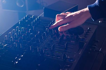 DJ hand mixing music on audio board mixer