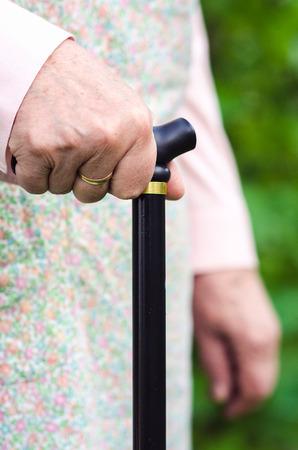 Old elderly woman holding a walking stick closeup