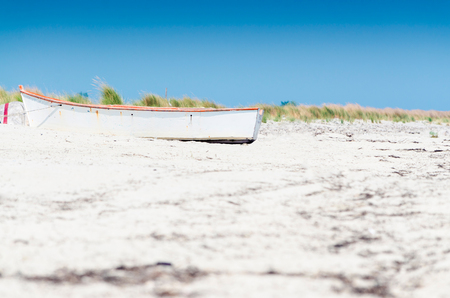 Small white boat on the sandy beach Stock Photo