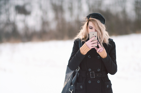 Young blond alternative girl in black clothes looking at phone