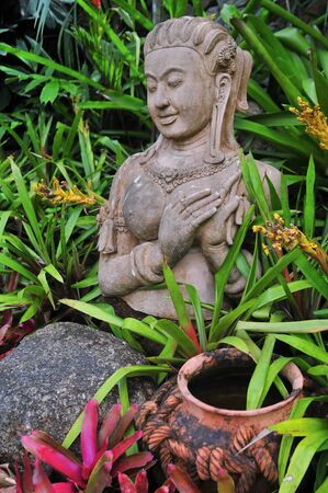 Statue of a buddhist goddess in the midst of green and colorful plants, stones and pottery photo