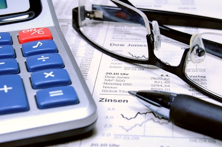Calculator, ball-pen and glasses on top of a stock exchange report  photo