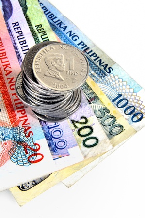 pesos: Philippine piso coins on a stack of banknotes