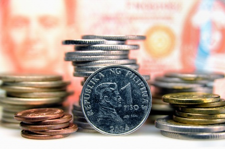 pesos: Philippine money coins in front of a 50 peso banknote