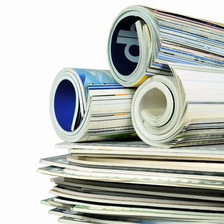 Diverse gestapeld en rolde tijdschriften op wit wordt geïsoleerd Stockfoto