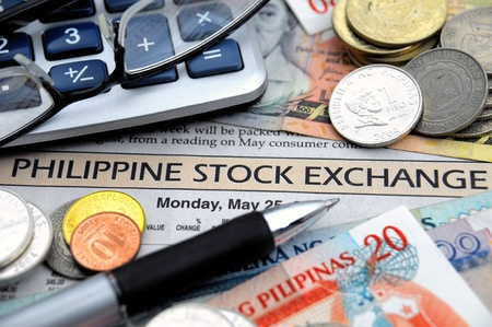 pinay: Currency, glasses and ball pen on a stock market repeort