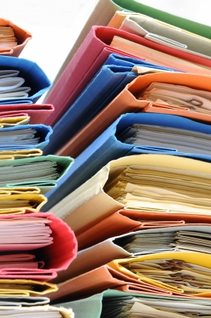 Two large stacks of colorful binders with white background