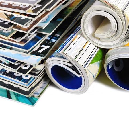 Verschillende gestapeld en rolde tijdschriften op wit wordt geïsoleerd