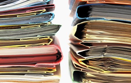 Two stacks of multicolored folders with documents on white background