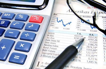 data sheet: Calculator, ball-pen and glasses on top of a stock exchange report