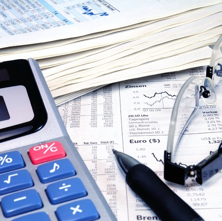 Calculator, ball-pen and glasses on top of a stock exchange report  Stock Photo - 11779232