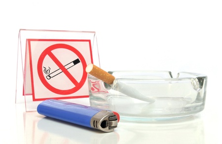 Smoking not allowed - Blue lighter, ashtray with cigarette and no smoking sign on white background photo