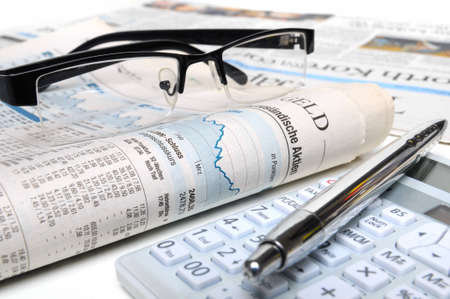 Calculator, ball-pen and glasses on top of a stock exchange report Stock Photo - 12721538