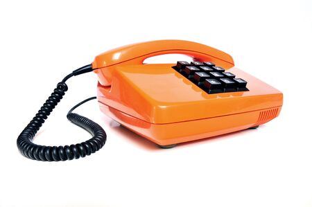 Orange colored vintage telephone with phone keypad and receiver on white background photo