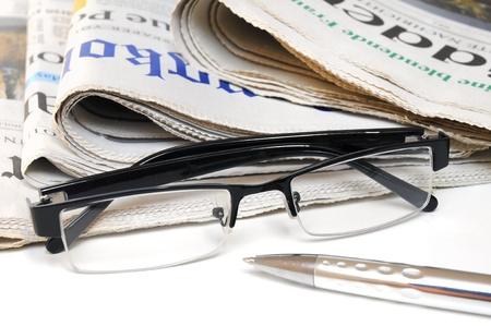 Krant, glazen en balpen op een witte achtergrond