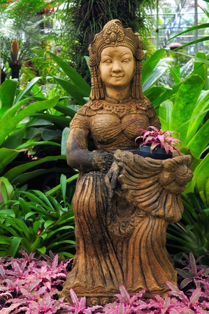 thai orchid: Statue of a buddhist goddess in the midst of green and colorful plants, stones and pottery