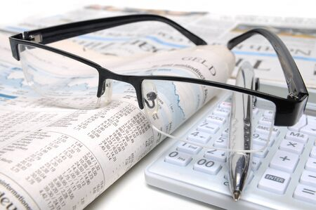 Ball point, glasses and a calculator on top of a chart report