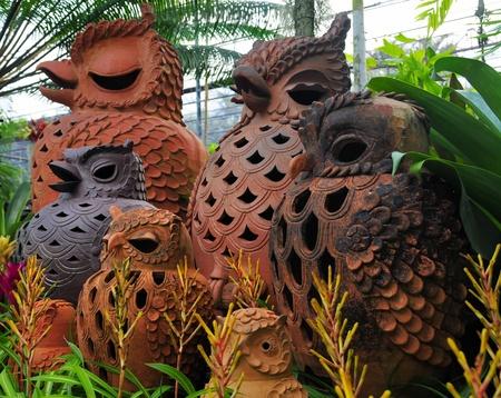 Terracotta owls between green plants  photo