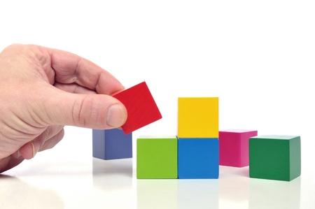 Laatste stap naar succes - Menselijke hand en veelkleurige speelgoed blokken op een witte achtergrond