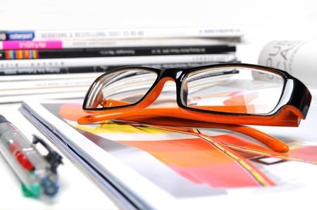 Verschillende tijdschriften met oranje gekleurde bril en balpen op een witte achtergrond
