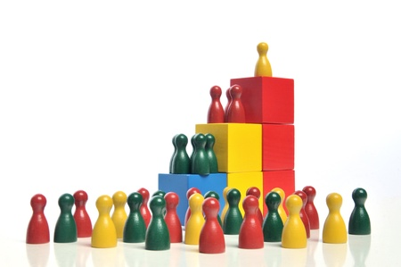 finance director: Hierarchy - Multicolored wooden toy blocks and figures on white background