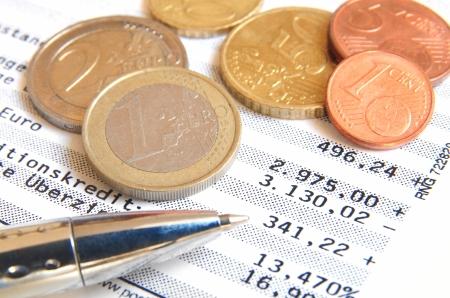 Euro munten en balpen op de top van een bankafschrift