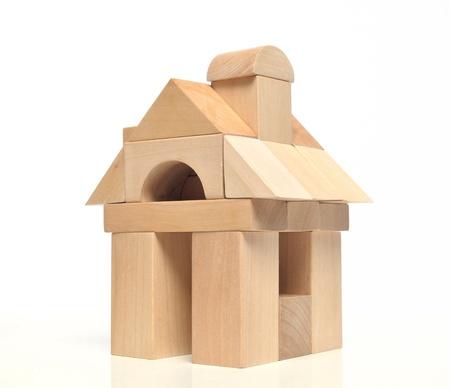 Little weekendhuis met natuurlijke gekleurde speelgoed blokken op witte achtergrond Stockfoto