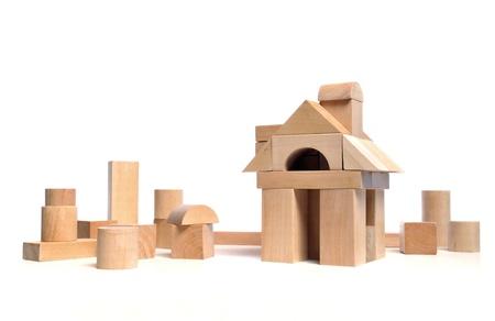 Stadje huis van natuurlijke gekleurde speelgoed blokken op witte achtergrond