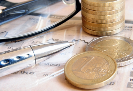 Geld munten, bril en bal pen op de top van een licht roze gekleurde beurs verslag