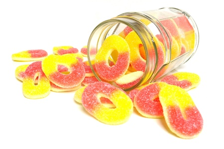 Peach flavored candy rings and glass jar on white background