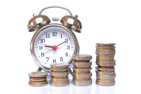 Time is money - Alarm clock and piles of Euro coins on white background