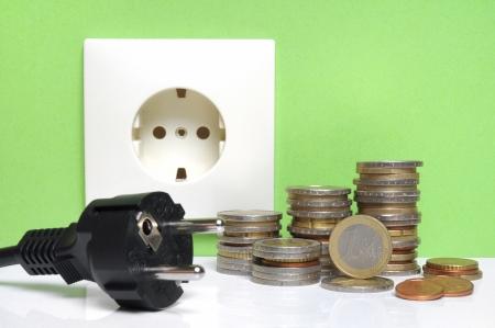 enchufe de luz: Ley de la Electricidad - enchufe y monedas de euro frente a una pared verde con el zócalo