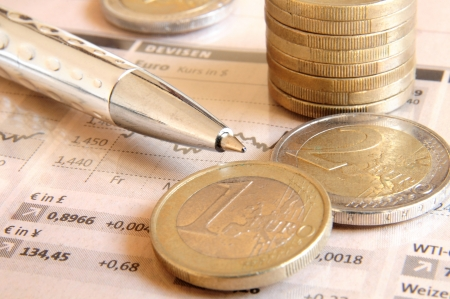 fx: Euro money coins and silver colored ball pen on top of stock market chart  Stock Photo