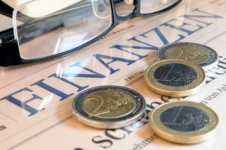 Euromunten, zwarte bril en de belettering financiën in de Duitse taal Stockfoto