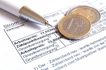 Witte bal pen en geld munten op de top van een energierekening Stockfoto